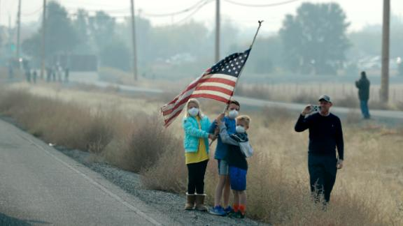 A group of children hold an American flag as the motorcade of President Donald Trump drives through Chico, California, on November 17.