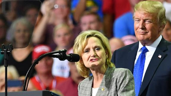 "Senator Cindy Hyde-Smith (L) stands on stage with US President Donald Trump at a ""Make America Great Again"" rally at Landers Center in Southaven, Mississippi, on October 2, 2018. (Photo by MANDEL NGAN / AFP)        (Photo credit should read MANDEL NGAN/AFP/Getty Images)"