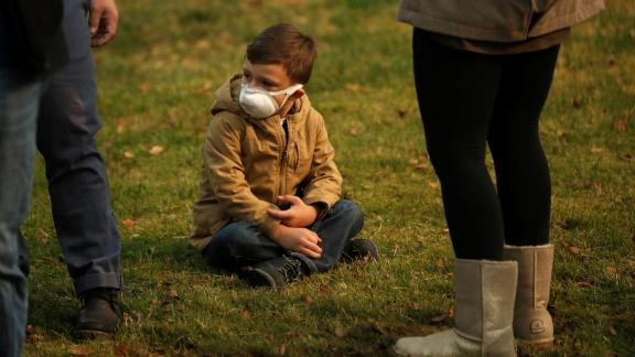 A child wears a smoke mask while watching President Trump