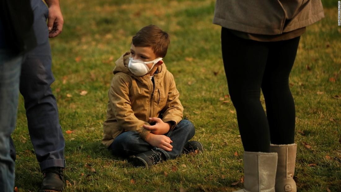 A child wears a smoke mask while watching President Trump''s motorcade in Chico on November 17.