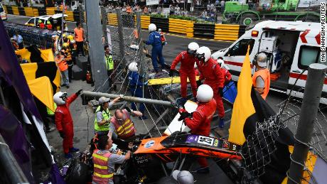 Race personnel and pit crew are seen at the accident site after Sophia Floersch flew over the barriers and crashed into a fence during a Formula Three race at the Macau Grand Prix.