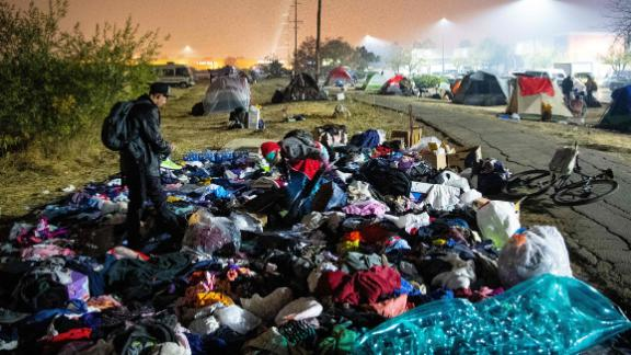 A wildfire evacuee sifts through a pile of clothing at a tent city in a Walmart parking lot in Chico, California, on Saturday, November 17.