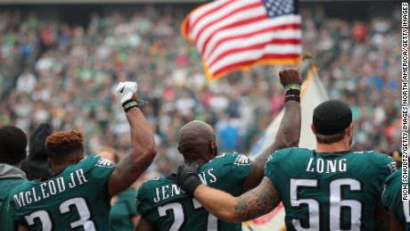 Chris Long (#56) shows solidarity with Philadelphia Eagles teammates Malcolm Jenkins (#27) and Rodney McLeod (#23) during the playing of the US national anthem on October 8, 2017 in Philadelphia. Two weeks earlier, President Donald Trump used a profanity to criticize protesting NFL players.