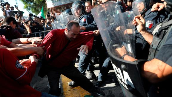 Demonstrators clash with police outside a migrant shelter as they protest the presence of thousands of Central American migrants in Tijuana on Sunday.