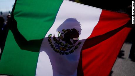 A demonstrator holds a Mexican flag outside a migrant shelter to protest the presence of thousands of Central American migrants in Tijuana, Mexico, on Sunday.