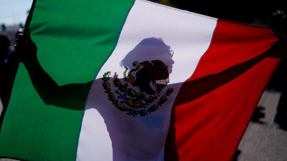 "A demonstrator holds a Mexican flag outside a migrant shelter to protest the presence of thousands of Central American migrants in Tijuana, Mexico, Sunday, Nov. 18, 2018. Protesters accused the migrants of being messy, ungrateful and a danger to Tijuana; complained about how the caravan forced its way into Mexico, calling it an ""invasion,"" and voiced worries that their taxes might be spent to care for the group as they wait possibly months to apply for U.S. asylum."