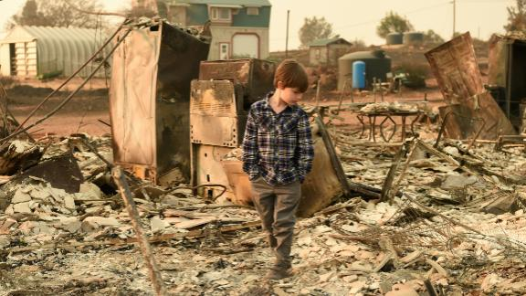 Jacob Saylors, 11, walks through the remains of his home Sunday in Paradise, California.