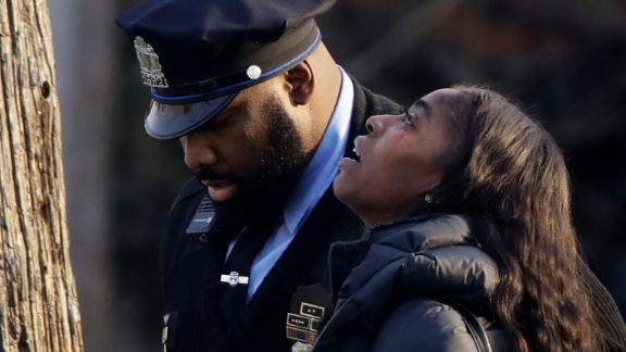 Nadirrah Smith is escorted from the scene of a fatal shooting in Philadelphia, Monday, Nov. 19, 2018. Police say two men and two women have been found shot and killed in a basement in Philadelphia. (AP Photo/Matt Rourke)