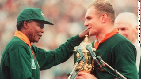 South African rugby team captain, Francois Pienaar (R), is congratulated by South African President Nelson Mandela (L) after South Africa won the Rugby World Cup final against New Zealand 24 June 1995.