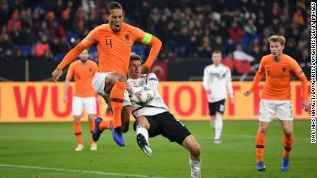 Dutch captain Virgil van Dijk battles for possession with Thomas Muller of Germany during their UEFA Nations League A1 match.