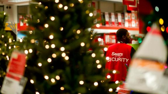 A security guard stands near a Christmas tree display at a Sears Holdings Corp. store ahead of Black Friday in Peoria, Illinois, U.S., on Thursday, Nov. 28, 2013. U.S. retailers will kick off holiday shopping earlier than ever this year as stores prepare to sell some discounted items at a loss in a battle for consumers. Photographer: Daniel Acker/Bloomberg via Getty Images