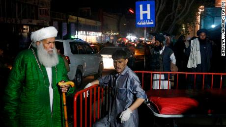Afghan religious scholars wait outside the hospital after a suicide bomber targeted a gathering.