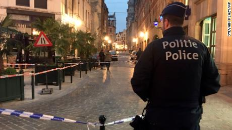 A police officer stands behind a police tape during investigations at a stabbing scene in the center of Brussels on Tuesday.