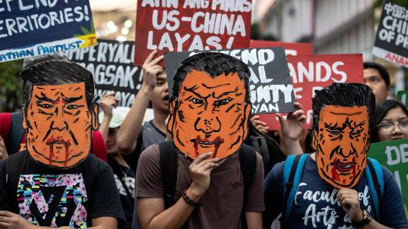 Protesters holds caricatures of Xi Jinping during a protest in Manila.