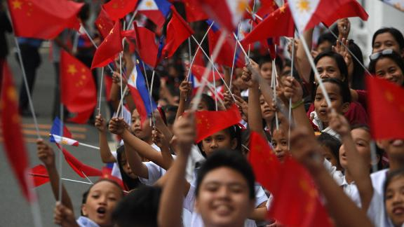 Schoolchildren wave the  flags of the Philippines and China as they line up November 20 along the route of China