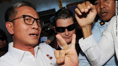 Renae Lawrence (center, wearing sunglasses) is escorted from prison in Bali on Wednesday after serving 13 years.