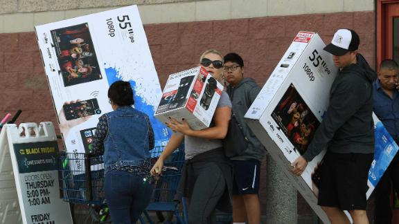 """Shoppers with their arms full walk to their cars during the """"Black Friday"""" sales at a Best Buy store in Culver City, California on November 25, 2016.US retailers kicked off the unofficial start of the holiday retail season with sales that begin on the Thanksgiving holiday. / AFP / Mark RALSTON        (Photo credit should read MARK RALSTON/AFP/Getty Images)"""