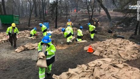 California Conservation Corps members fill out sandbags ahead of significant rain.
