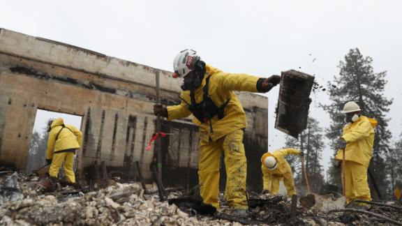 PARADISE, CALIFORNIA - NOVEMBER 21: Search and rescue crews dig through the burnt remains of a business as they search for human remains on November 21, 2018 in Paradise, California. Fueled by high winds and low humidity the Camp Fire ripped through the town of Paradise charring over 150,000 acres, killed at least 81 people and has destroyed over 18,000 homes and businesses. The fire is currently at 80 percent containment and hundreds of people still remain missing. (Photo by Justin Sullivan/Getty Images)