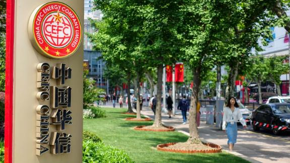 Pedestrians walk past a signboard of China CEFC Energy in Shanghai, China, in May 2018.
