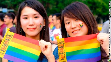 Two young women hold rainbow flags in support of same sex marriage during a gay pride parade in Taipei October, 2018.