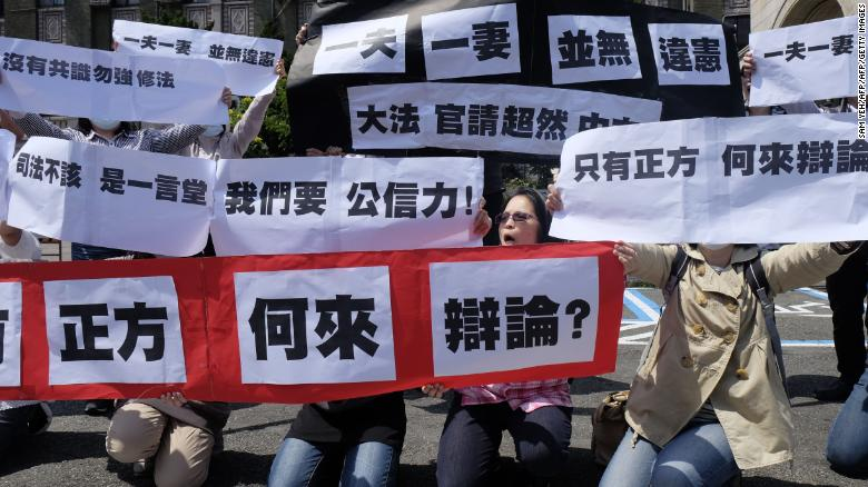 "Conservative activists display signs reading ""one husband, one wife does not go against the constitution"" in Taipei, on March 24, 2017."