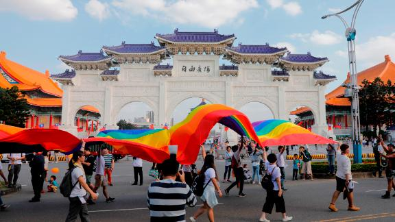 Participants walk with a rainbow banner past the Chiang Kai-shek Memorial Hall during a gay pride parade in Taipei on October 27, 2018.