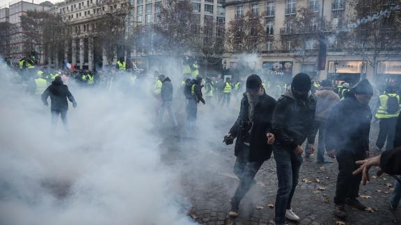 Protesters clash with riot police who fired tear gas canisters Saturday in central Paris.
