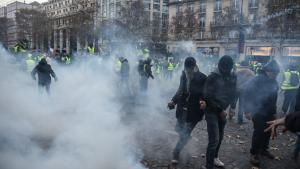 Protestors clash with riot police amid tear gas during a demonstration of Yellow vests (Gilets jaunes) on the Champs Elysees in Paris, on November 24, 2018 during a protest against rising oil prices and living costs. - Demonstrators who have blocked French roads over the past week dressed in high-visibility jackets, are set to cause another day of disruption on November 24 amid calls to bring Paris to a standstill. (Photo by Lucas BARIOULET / AFP) (Photo credit should read LUCAS BARIOULET/AFP/Getty Images)