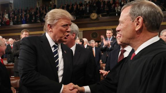 US President Donald J. Trump (L) shakes hands with Chief Justice John Roberts (R) as he arrives to deliver his first address to a joint session of Congress from the floor of the House of Representatives in Washington, DC, USA, 28 February 2017.   / AFP / POOL / JIM LO SCALZO        (Photo credit should read JIM LO SCALZO/AFP/Getty Images)