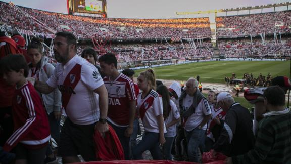 Fans of River Plate leave the stadium after the game was delayed multiple times and eventually postponed for Sunday.