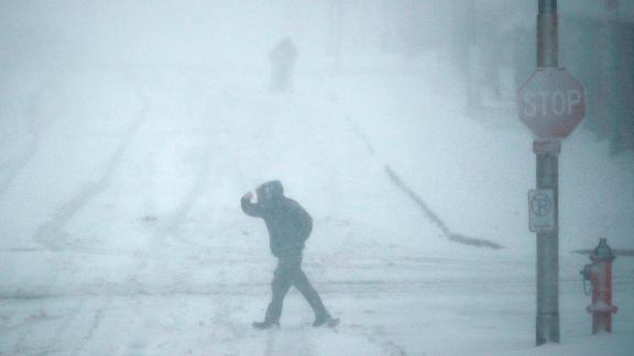 Pedestrians walk as snow falls Sunday, November 25, 2018, in Kansas City, Missouri. Blizzard-like conditions have closed highways and delayed air travel as a winter storm moves through the Midwest.