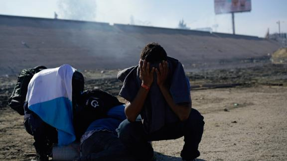 Migrants on the Mexico side of the border take cover from tear gas fired by US agents.