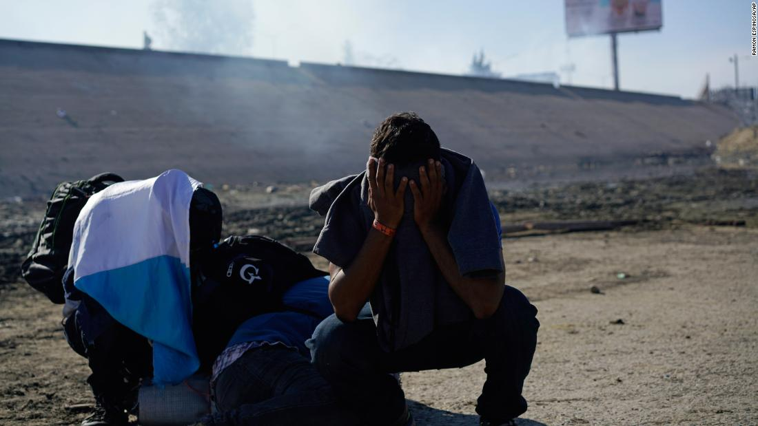 Three Honduran migrants huddle at the riverbank amid tear gas fired by US Customs and Border Protection.