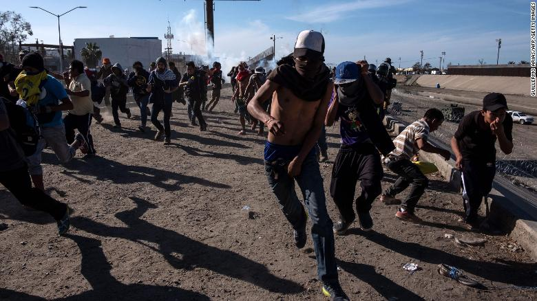 Migrants run along the Tijuana River near the US-Mexico border after US agents threw tear gas to disperse them.
