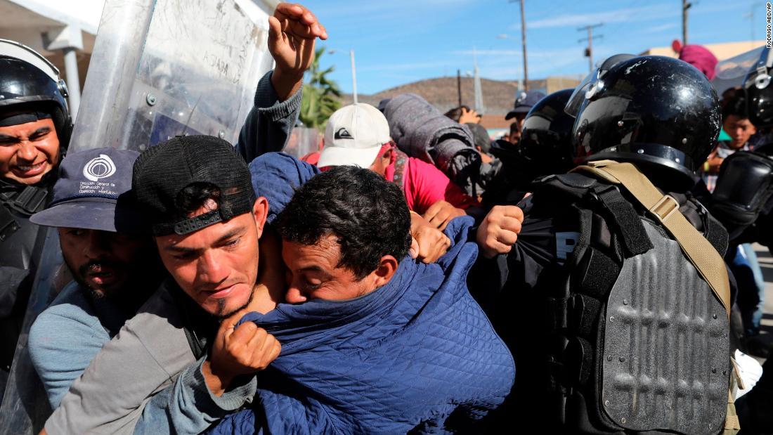 Migrants clash with Mexican police at the US-Mexico border after getting past another line of Mexican police in Tijuana on Sunday.