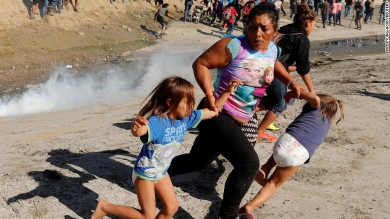 A migrant family from Honduras, part of a caravan of thousands traveling from Central America en route to the US, runs from tear gas released by US border patrol near the fence between Mexico and the United States in Tijuana, Mexico, November 25.