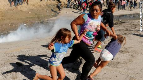 A migrant family runs from tear gas released by US border patrol agents near the fence between Tijuana, Mexico, and San Diego.