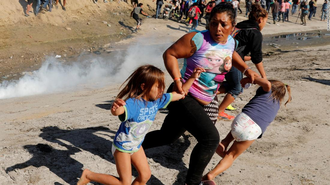 A migrant family from Honduras, hoping to reach the United States, runs from tear gas released by US Customs and Border Protection near the fence between Mexico and the United States in Tijuana on Sunday.
