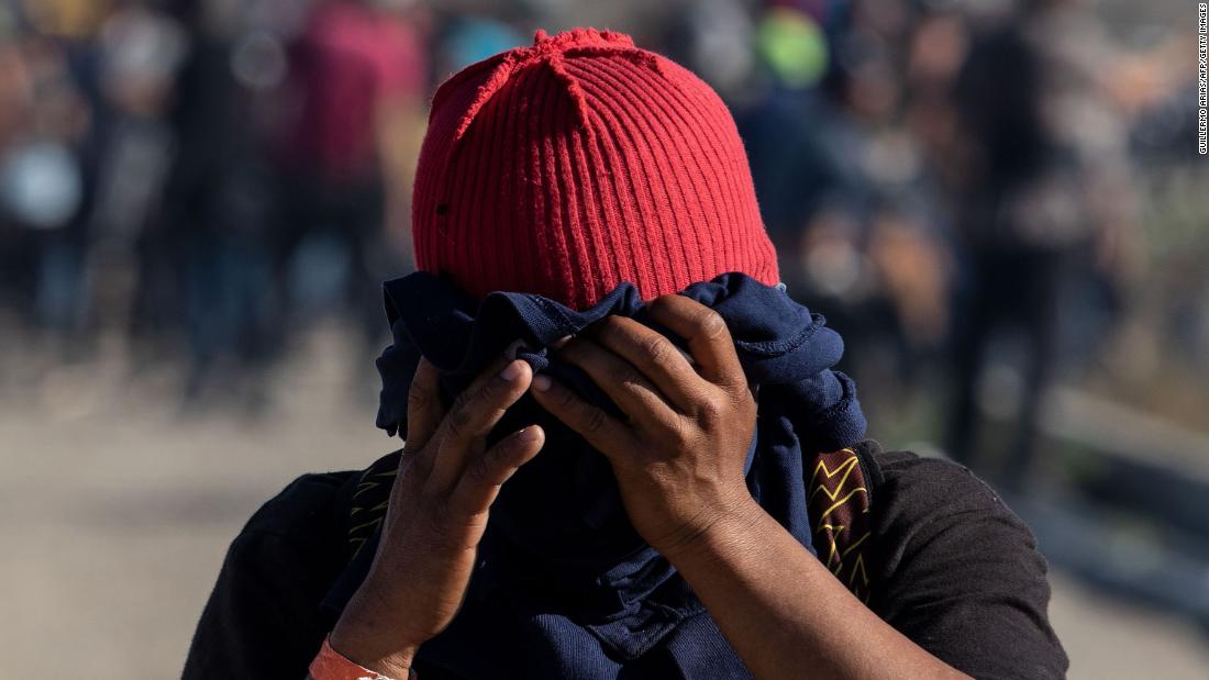 A migrant covers his face near the El Chaparral border crossing after US Customs and Border Protection used tear gas to disperse a crowd on Sunday.