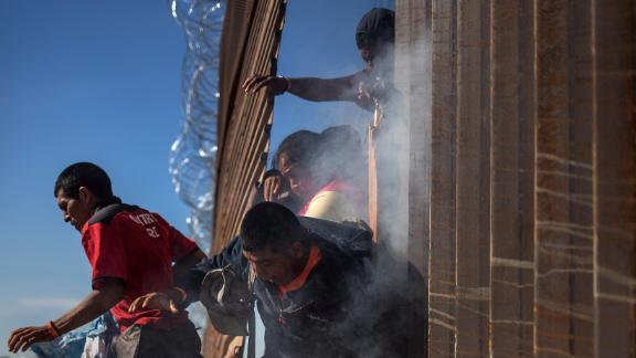 Migrants return to Mexico after tear gas was deployed.