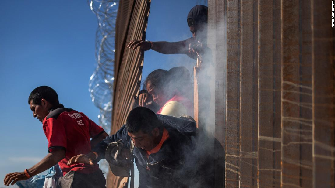 Migrants return to Mexico after US Customs and Border Protection deployed tear gas. The migrants were trying to illegally cross the border wall into the United States from Tijuana on Sunday.