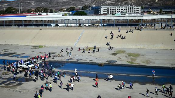 Migrants cross the riverbed of the Tijuana River as they try to get to the port of entry.