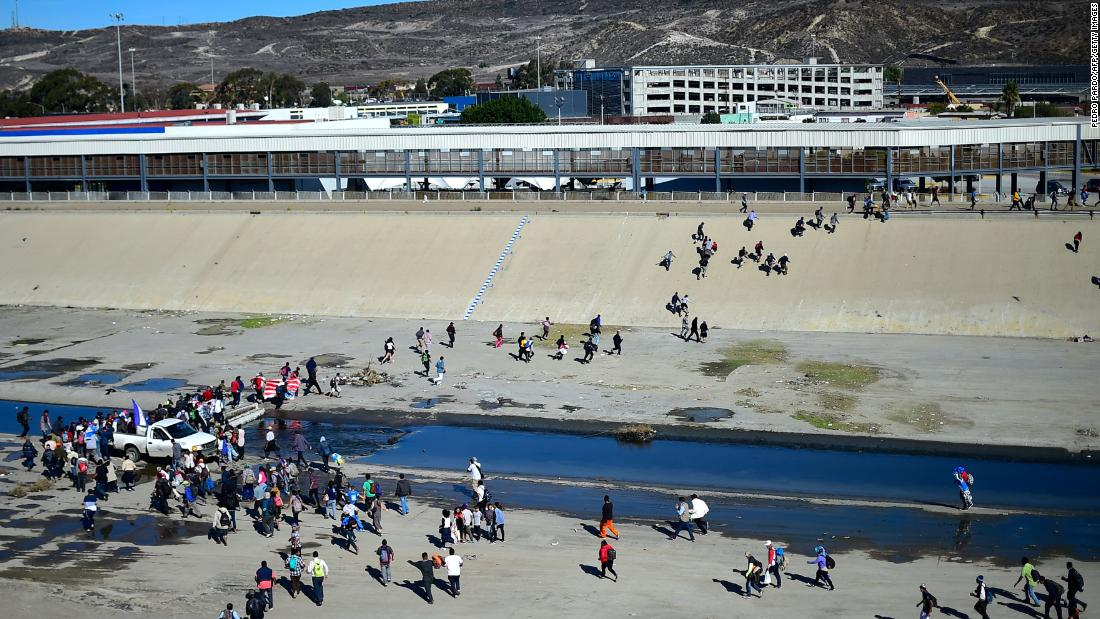 Migrants cross the almost dry riverbed of the Tijuana River in an attempt to get to El Chaparral Port of Entry in Tijuana on Sunday.