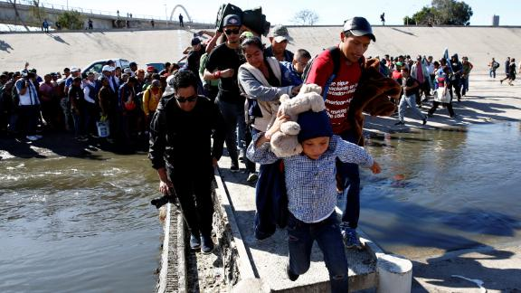 Migrants cross the Tijuana River to reach the border fence.