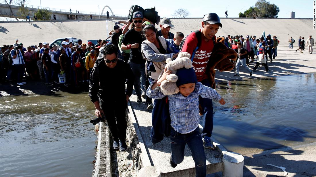 Migrants cross the Tijuana River to reach the border fence between Mexico and the United States in Tijuana.