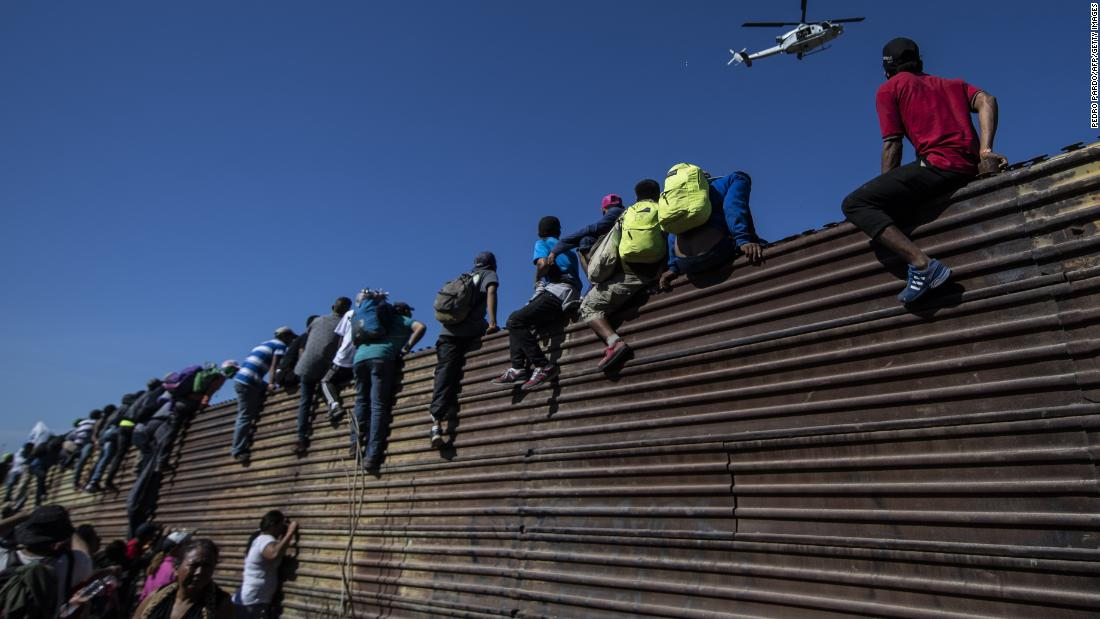Central American migrants climb a metal barrier on the Mexico-US border near El Chaparral border crossing in Tijuana, Mexico, on Sunday.