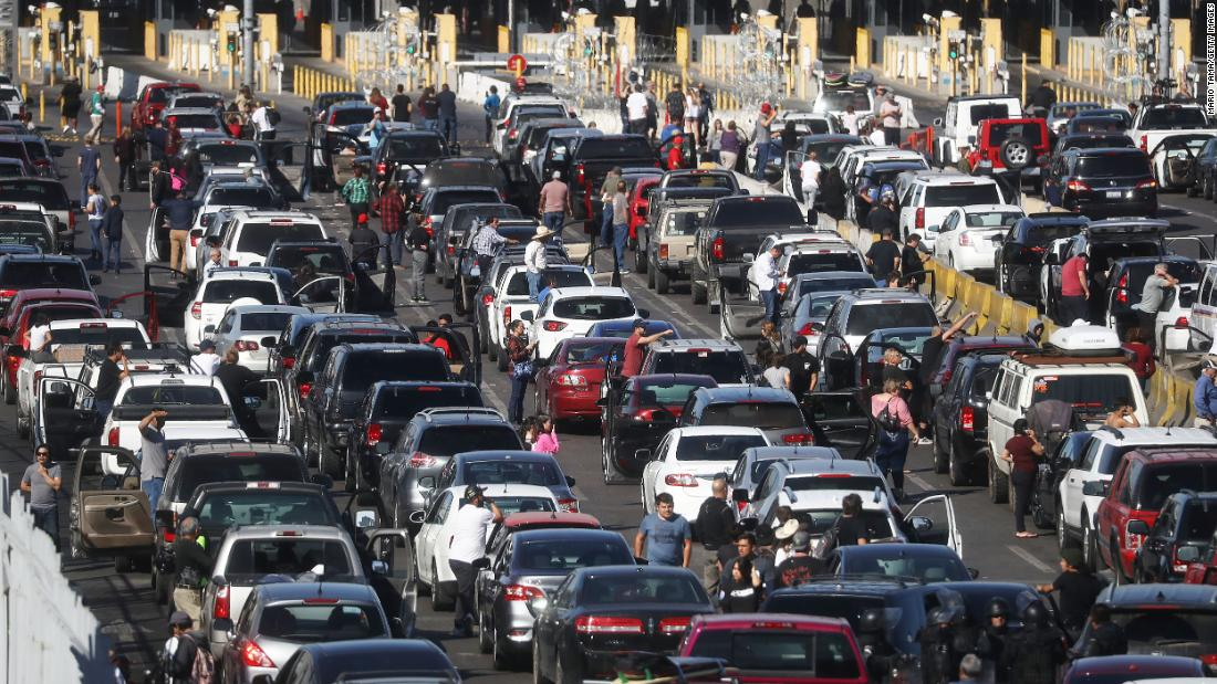 People attempting to cross into the United States gather near their vehicles as the San Ysidro Port of Entry stands closed at the US-Mexico border on Sunday in Tijuana. Migrants circumvented a police blockade at another port of entry and US Customs and Border Protection temporarily closed the two crossings in response.