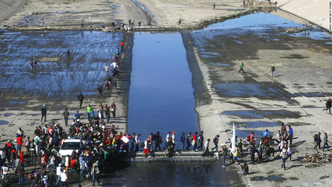 Migrants cross the nearly dry Tijuana River as they make their way around a police blockade toward the El Chaparral Port of Entry.