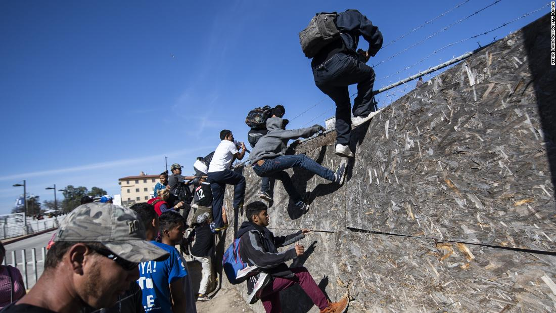 Migrants climb over a fence as they try to reach the US-Mexico border in Tijuana on Sunday.